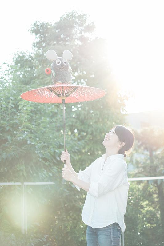 子供用の朱色番傘、そこに乗るフレデリック、そして夕日